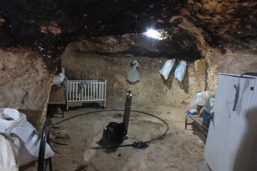 """Jinba: Unter einem zerstörten Haus bleibt noch die Höhle. Diese zuvor traditionelle Behausung stellt jetzt den Rückzugsort dar. Rechts im Bild der """"Batterieschrank"""" mit den aus Solarpanelen gespeisten Batterien. Diese wurden übersehen und daher durch das israelische Militär nicht konfisziert."""