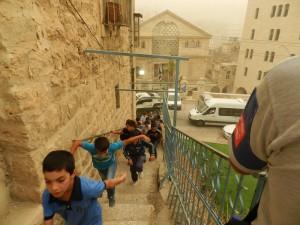 Schüler*innen auf der Treppe zur Cordoba Schule, gegenüber die Siedlung Beit Hadassah