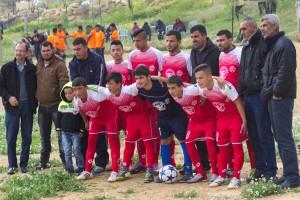 Die Mannschaft aus Susiya beim Gruppenbild, im Hintergrund in Orange die Spieler aus Um al Kheir