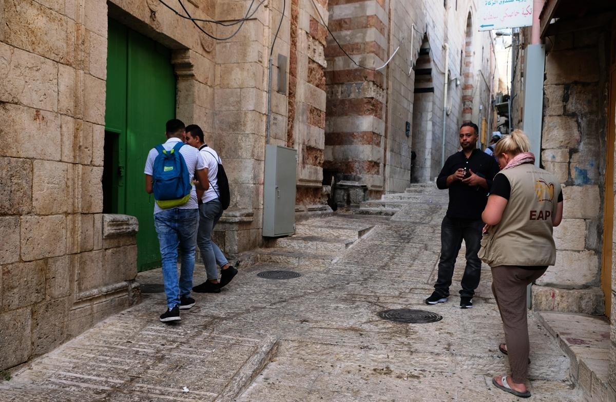 Im Gespräch – eine Ökumenische Begleiterin mit Bassam Khalil vor der Dar-al-Aytam-Schule in der Altstadt. Foto © EAPPI