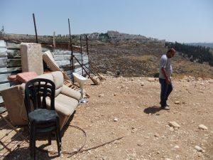 Die wenigen geretteten Habseligkeiten stehen am Wellblechzaun, im Hintergrund eine israelische Siedlung