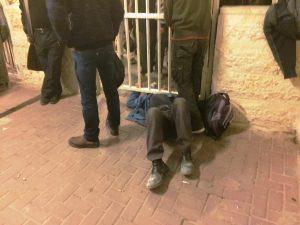 Ein Mann versucht, sich am Checkpoint unter einem Tor hindurchzuquetschen, um schneller voran zu kommen; Foto © EAPPI