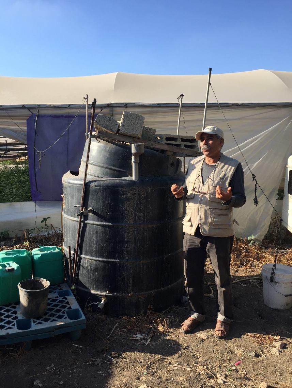 """Organischer Farmer Fayez und der Tank mit seinem Spezialdünger, der """"Suppe"""" (Photo: EAPPI)"""
