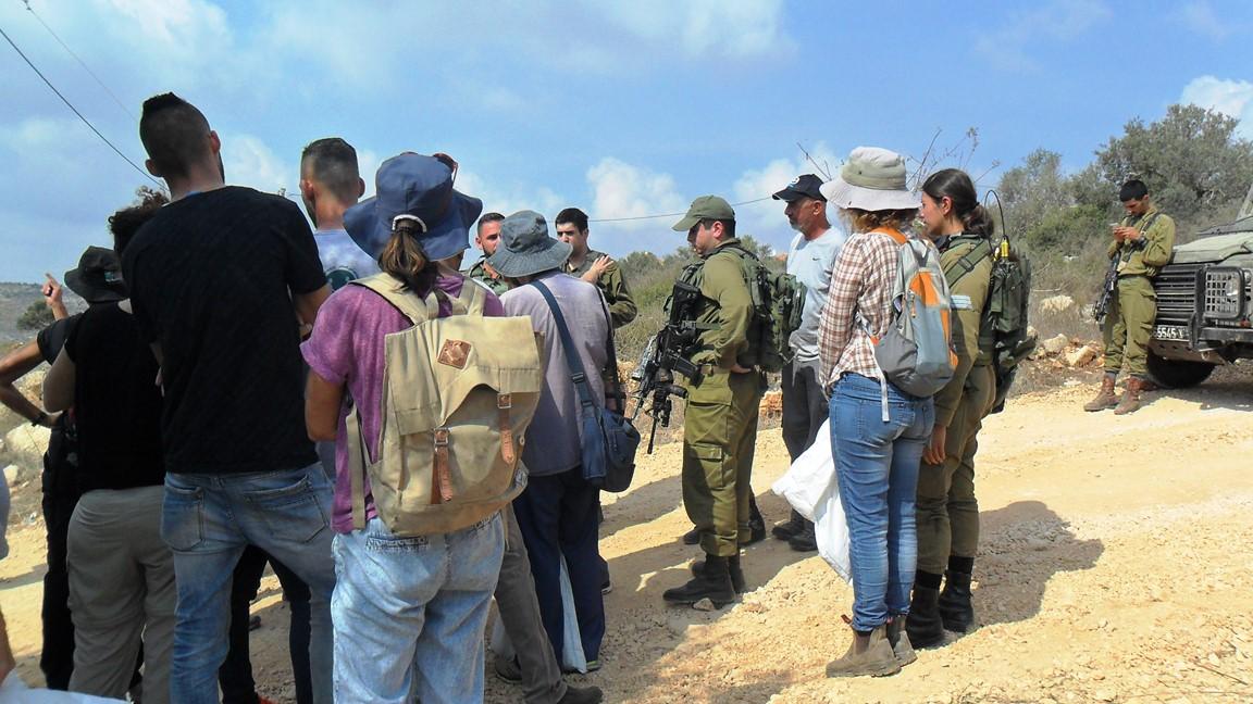 Bauern und freiwillige Helfer im Gespräch mit israelischen Soldaten in Haris, © EAPPI