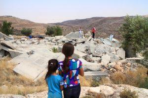 Geschwister vor den Trümmern der ehemaligen Wohngebäude; © EAPPI