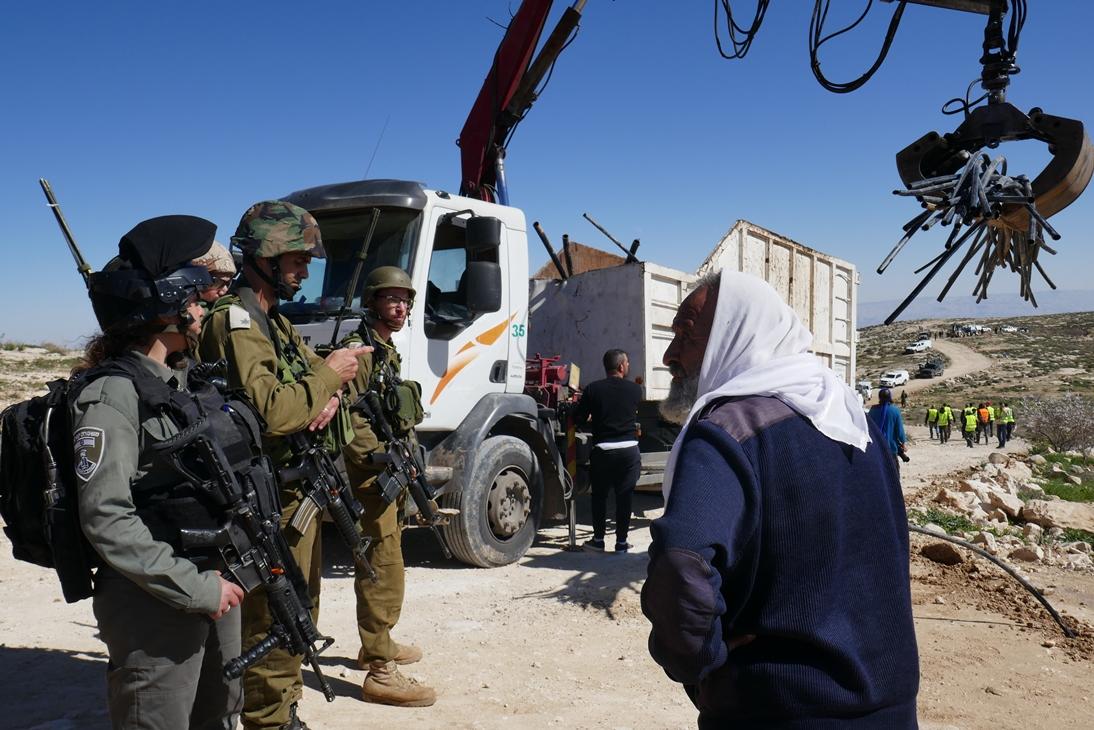 Ein lokaler Schäfer redet mit israelischen Soldaten während der Zerstörung der Wasserleitungen in Massafer Yatta; Foto © EAPPI