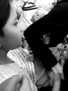 Ein Mädchen hält sich im Gedränge verzweifelt an ihrer Mutter fest, um nicht verloren zu gehen.