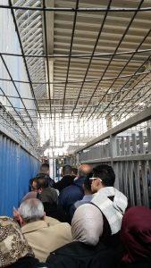 In enge Gittergänge gezwängt warten die Menschen am Checkpoint Qalandia