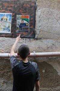 Mohammad und ein Solidaritätsplakat mit seinem Foto, das im Camp aufgehängt wurde. (Photo: EAPPI)