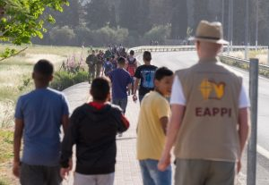 EA begleitet Schulkinder vorbei an einer Gruppe von Soldaten © EAPPI