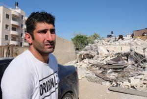 Ibrahim Rajabi vor den Trümmern seines Hauses. Foto © EAPPI
